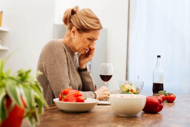 Küchentisch. beunruhigte hellhaarige frau, die mit ihrem lebensstil depressiv ist, während sie allein alkohol trinkt