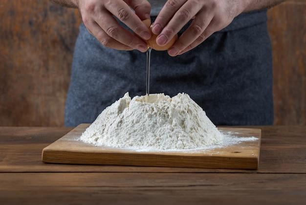 Küchentisch. männlicher bäcker, der teig an der bäckerei zubereitet