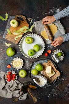 Küchentisch mit äpfeln, mehl, butter, erdbeeren und zitrone