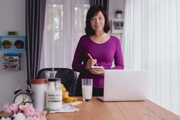 Küchentisch mit asiatischem älterem schreiben auf briefpapier für die zubereitung des lebensmittels.