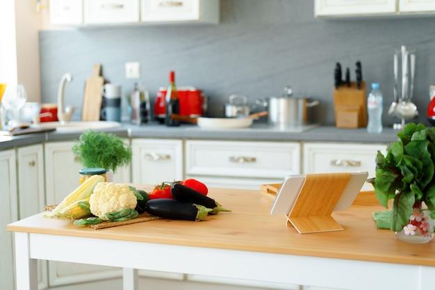 Küchentisch mit frischem gemüse und digitalem tablet