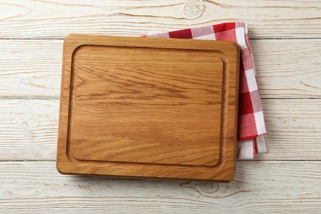 Küchentuch und holzbrett auf weißem holzhintergrund