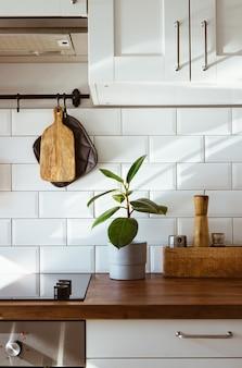Küchenutensilien aus messing, kochzubehör. hängende küche mit weißer fliesenwand und holztischplatte. grüne pflanze auf küchenhintergrund am frühen morgenlicht vertikal