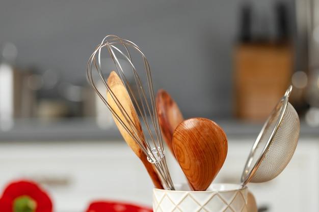 Küchenutensilien in einer tasse auf küchentisch schließen oben