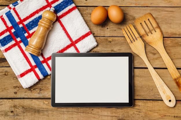 Küchenutensilien mit einer tablette auf rustikalem tisch