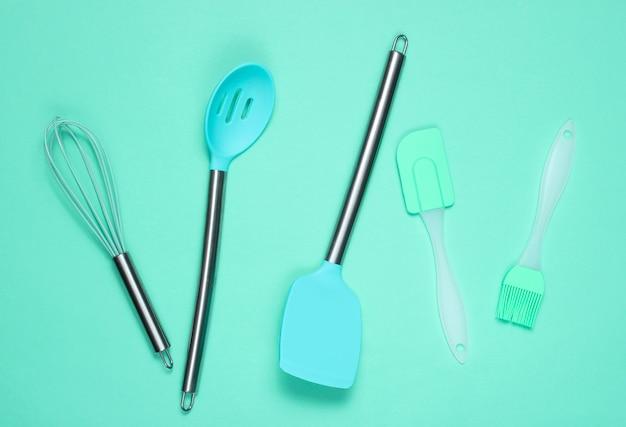 Küchenutensilien-set: küchenbürste und schneebesen, spatel auf blau. draufsicht