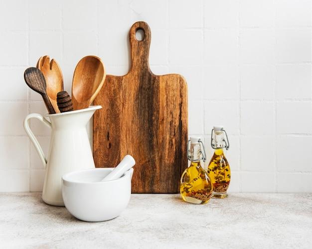 Küchenutensilien, werkzeuge und geschirr auf der oberfläche der weißen fliesenwand