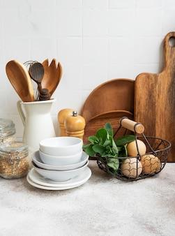 Küchenutensilien, werkzeuge und geschirr auf der weißen fliesenwand des hintergrundes. interieur, moderner küchenraum in hellen farben. leerzeichen für einen text, vorderansicht