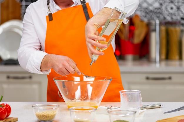 Küchenvorbereitung: der küchenchef mischt die zutaten in der schüssel