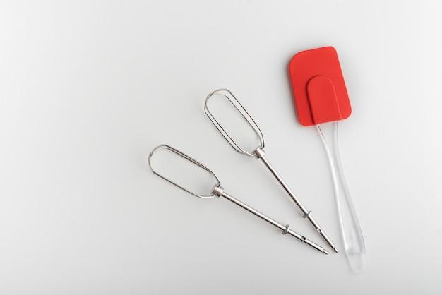 Küchenwerkzeuge mixer whiskas und küchensilikonspatel auf weißem hintergrund.