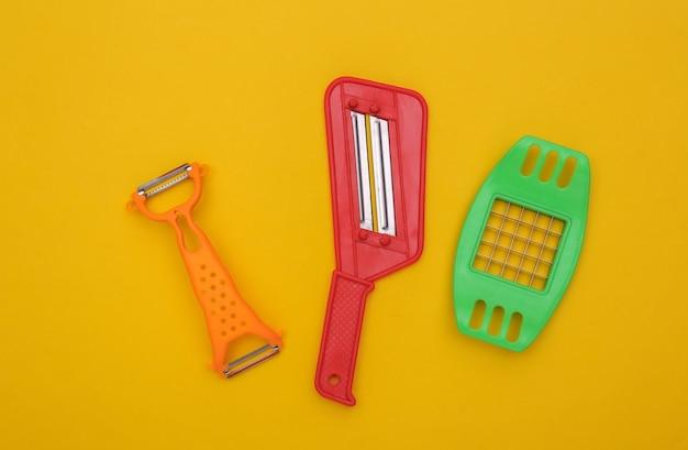 Küchenwerkzeuge zum schneiden von gemüse und messer zum schälen der haut auf gelbem hintergrund. ansicht von oben