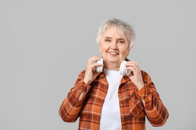 Kühle ältere frau mit kopfhörern auf grauer oberfläche