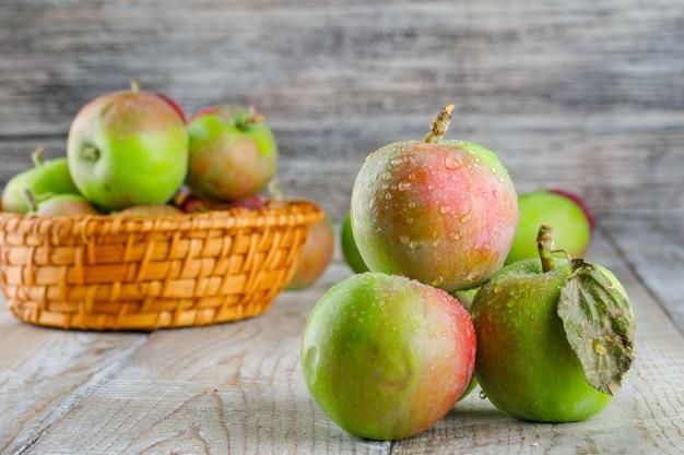 Kühle äpfel in einem weidenkorb auf holz. seitenansicht.
