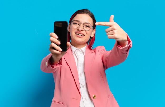 Kühle frau des roten haares mit einem smartphone