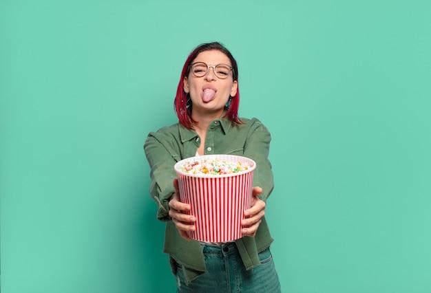 Kühle frau des roten haares mit popcorns und einer fernbedienung des fernsehers