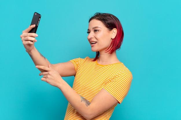 Kühle frau des roten haares unter verwendung eines smartphones.