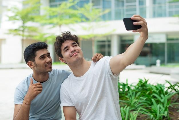 Kühle hübsche jungs, die auf frontkamera von smartphone fotografieren