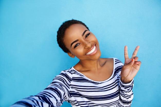 Kühle junge schwarze frau, die selfie mit friedenshandzeichen nimmt
