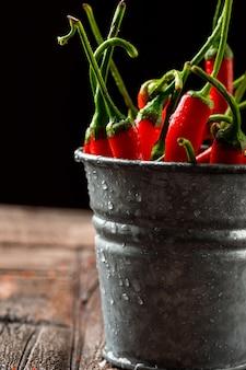 Kühle rote paprika in einer mini-eimer-nahaufnahme auf steinfliesen und schwarz