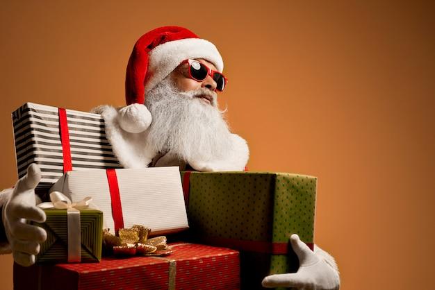 Kühle santa claus in der sonnenbrille, die farbige geschenkboxen hält