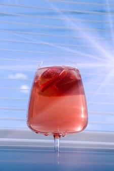 Kühlende erdbeer-sangria mit sekt, erdbeere, eiswürfel im sektglas