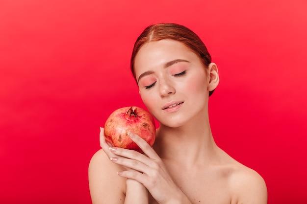 Kühlende frau, die granat auf rotem hintergrund hält. studioaufnahme des entspannten ingwermädchens mit granatapfel.