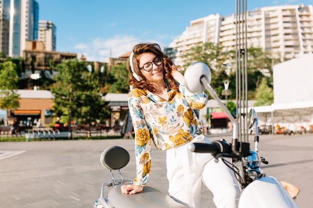 Kühlende junge dame in der weinlesebluse mit blumenmuster, die auf moped sitzt und musik mit bäumen und wolkenkratzern hört