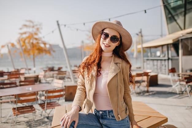 Kühlende junge frau im lässigen outfit, das durch sonnenbrille mit lächeln sitzt, das auf tisch sitzt