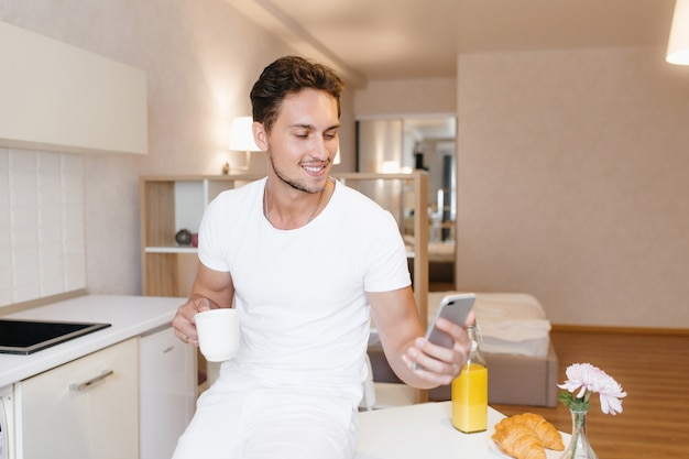 Kühlender bärtiger mann im weißen outfit schaut auf smartphone-bildschirm, kaffee zu hause trinkend