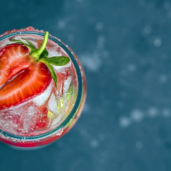 Kühlender italienischer alkoholischer rossini-cocktail mit sekt, erdbeere, eiswürfeln im sektglas