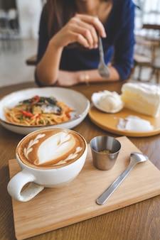 Kühlender tag der glücklichen frau im kaffeecaféshop mit heißem latte und süßem weißem kuchen