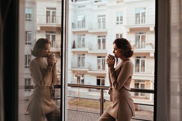 Kühlendes brünettes mädchen, das mit tasse leckerem tee aufwirft. foto der prächtigen jungen frau trinken kaffee nahe fenster.