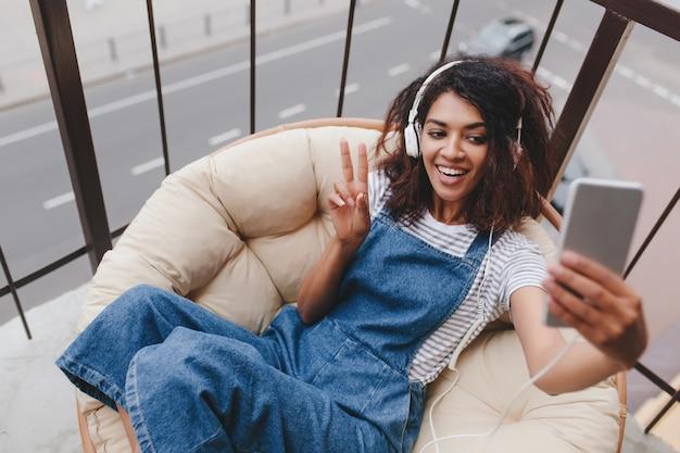 Kühlendes lockiges mädchen mit glücklichem lächeln, das selfie macht, während auf balkon liegend