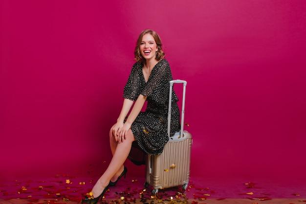 Kühlendes mädchen im weinlesekleid, das auf koffer mit schüchternem lächeln sitzt. romantische blonde dame posiert vor der reise mit vergnügen.