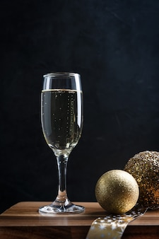 Kühler funkelnder champagner im hohen flötenglas mit goldenen weihnachtskugeln auf hölzerner bartheke
