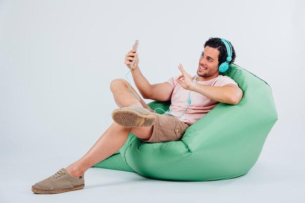 Kühler mann auf couch mit selfie mit smartphone