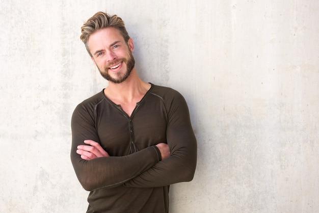Kühler moderner mann, der mit den armen gekreuzt lächelt