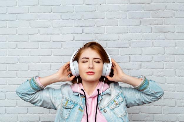 Kühles mädchen der hübschen mode, das musik in den kopfhörern hört