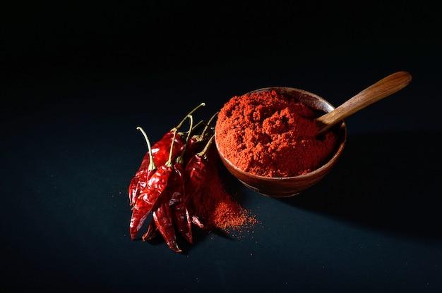 Kühles pulver in der holzschale mit roten kühlen, getrockneten chilis auf schwarzem hintergrund
