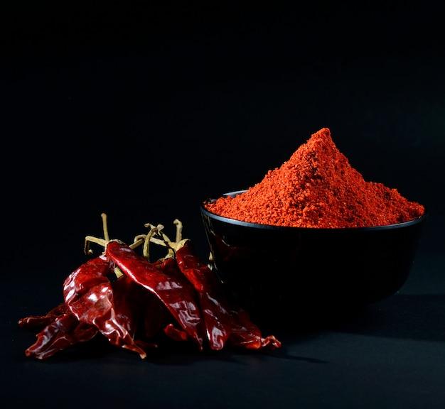 Kühles pulver in der schwarzen schüssel mit roten kühlen, getrockneten chilis auf schwarzem hintergrund