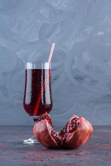Kühles und frisches glas granatapfelsaft und frischer bio-granatapfel