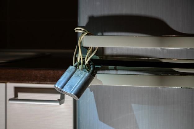 Kühlschrank abschließen. metallvorhängeschloss, das am kühlschrank hängt. konzept des essens in der nacht, abnehmen, fettleibigkeit