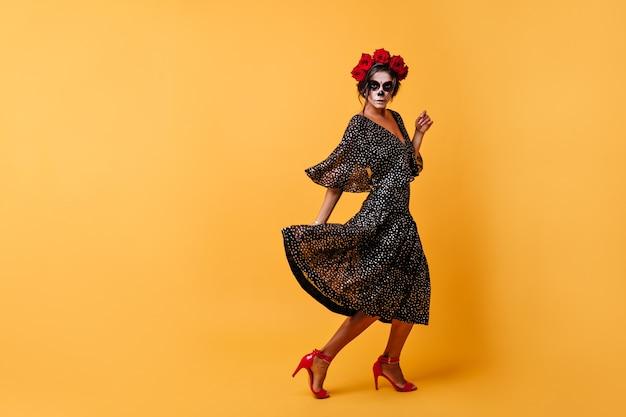 Kühnes tanzendes mädchen mit dunklem haar, das mit kranz aus natürlichen blumen auf ihren kopf gestochen wird, bewegt sich und posiert mit schwarzem kleid und zombiemaske