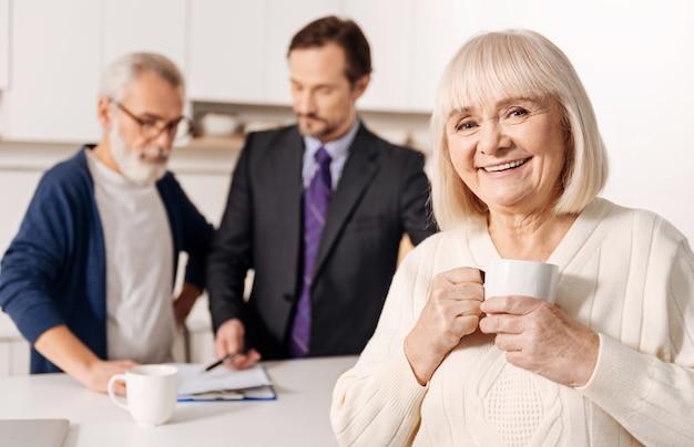 Kümmere dich um dein leben. charmante entzückende lächelnde alte frau, die steht und sich ausruht, während ihr ehemann dokumente mit anwalt unterschreibt