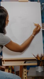 Künstler der afroamerikanischen ethnizität, der vase auf weißer leinwand mit bleistift und bastelwerkzeugen im studio zeichnet. schwarze junge frau, die authentisches design für neue meisterwerke und bildende kunst schafft