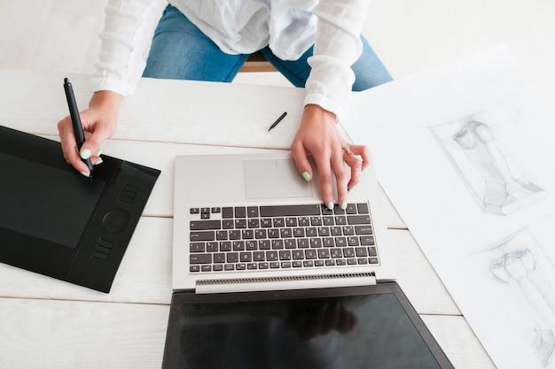 Künstler, der an der draufsicht des laptops und des grafiktabletts arbeitet