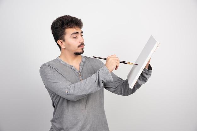 Künstler, der an einem neuen projekt auf der leinwand arbeitet.