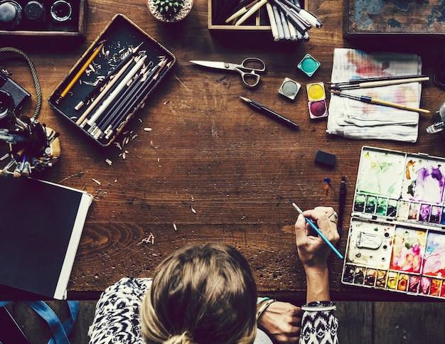 Künstler, der an ihrem arbeitsplatz sitzt