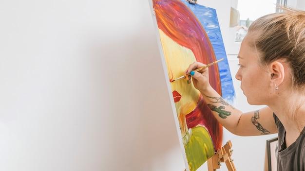 Künstler, der bild auf gestell zeichnet