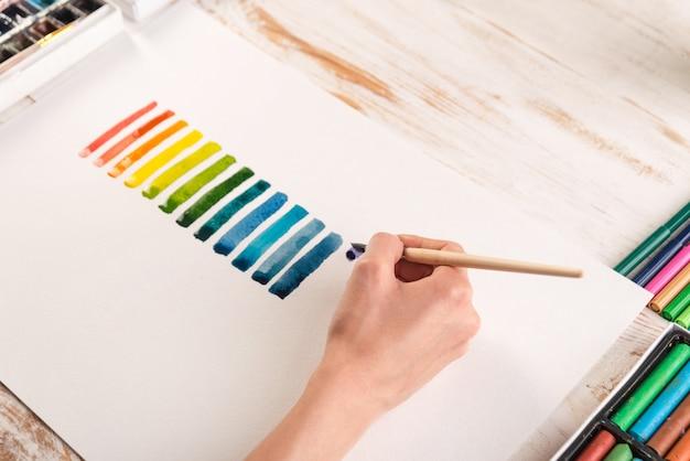 Künstler, der bunte streifen mit pinsel auf weißem papier malt